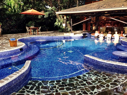 Main pool at Nayara Hotel with fun swim-up bar and swim-up tables